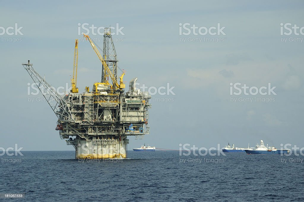 Oil production platform and seismic vessels stock photo