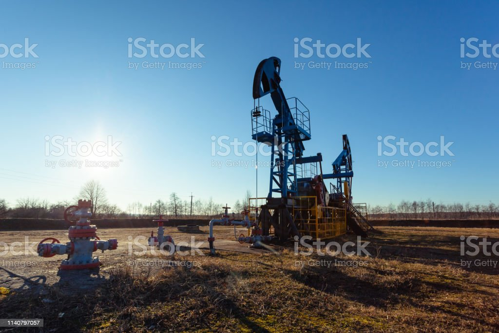 oil production tower while working against the bright sun and blue sky