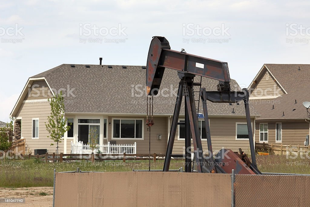 Oil pump jack and homes Frederick Colorado stock photo