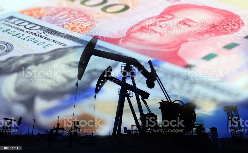Oil pump on background of US dollar and RMB, stock photo