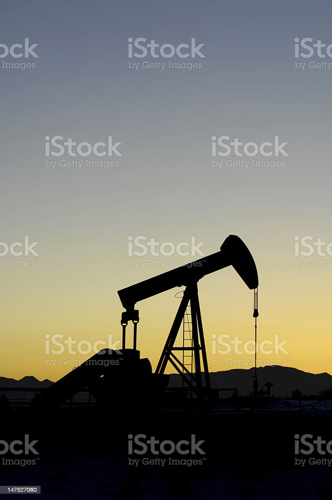 Oil Pump silhouetted against a mountain sunset royalty-free stock photo