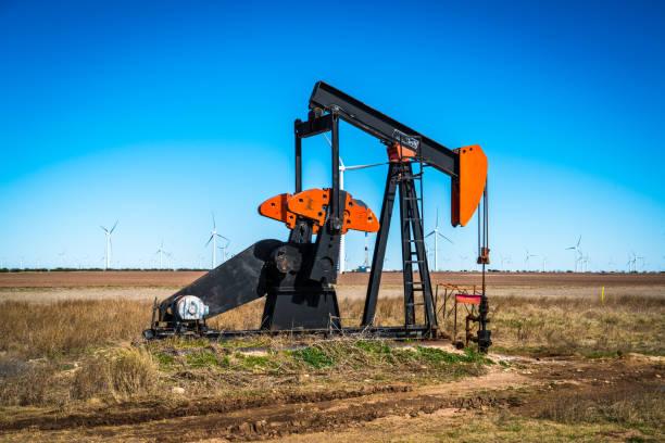 Ölpumpe umgeben von massivem Windpark im Westen von Texas – Foto