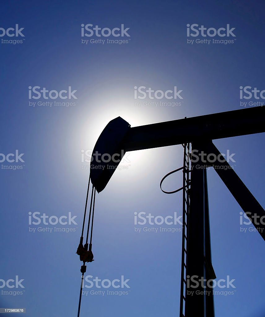Oil Pumpjack Silhouetted Against Blue Sky royalty-free stock photo