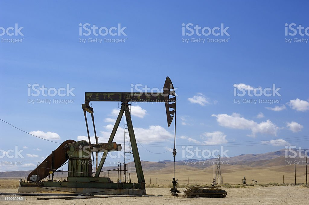 Oil Pumpjack with Clouds and Hills in Background stock photo