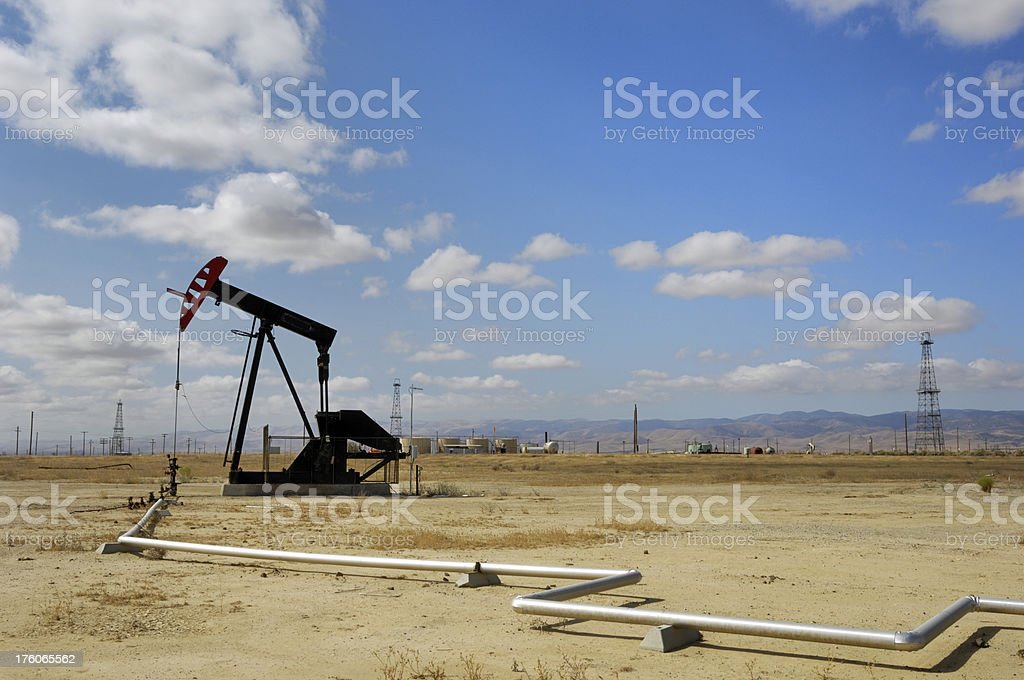 Oil Pumpjack with Clouds in Background stock photo