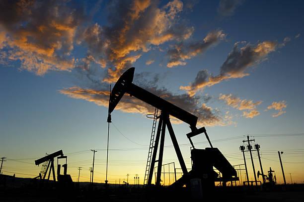 Oil Pumpjacks Against a Sunset Sky stock photo