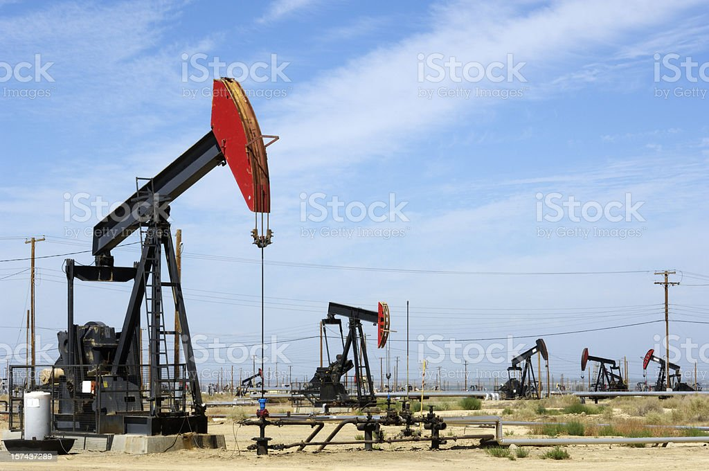 Oil Pumpjacks Under Cloud Filled Sky stock photo