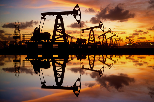 Pump jack silhouette against a sunset sky with reflections in the water.