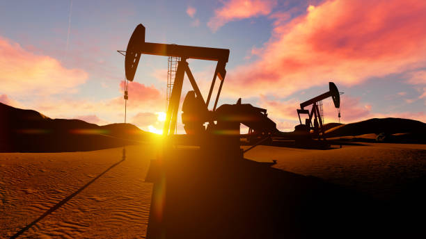Oil pumps in the desrt over dusk sun. stock photo