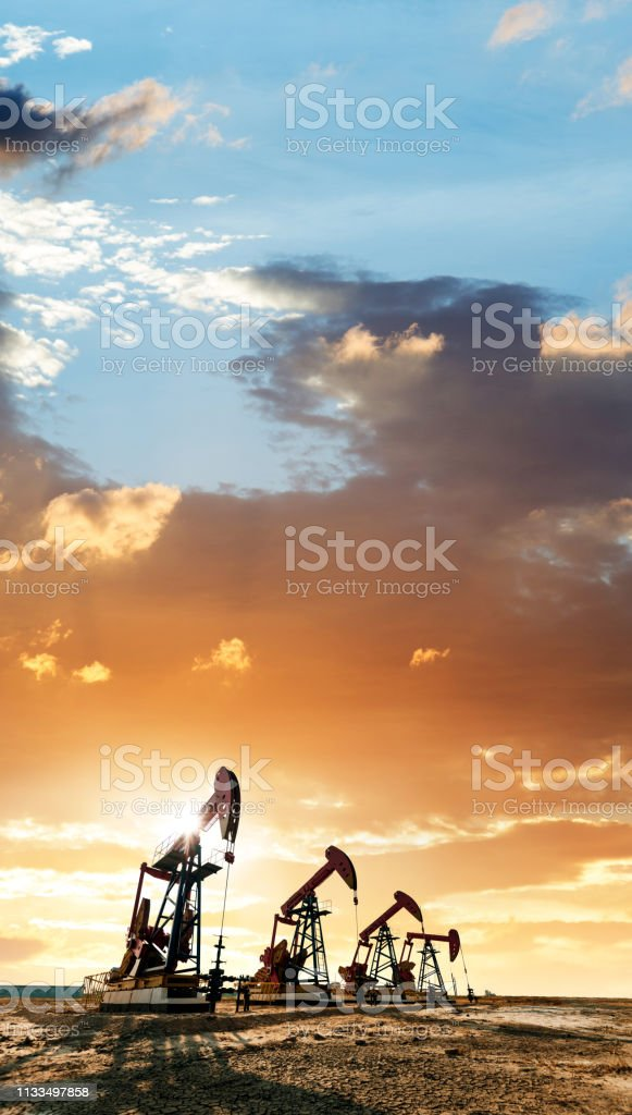 Oil pumps working under the sunrise sky stock photo