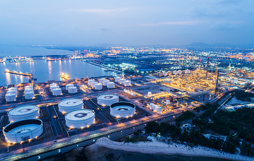 Aerial view or top view night light oil terminal is industrial facility for storage of oil and petrochemical. oil manufacturing products ready for transport and business transportation.