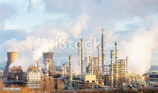 Steam and smoke rising from distillation towers and cooling towers towards the left at Grangemouth oil refinery and petrochemical plant in Central Scotland.