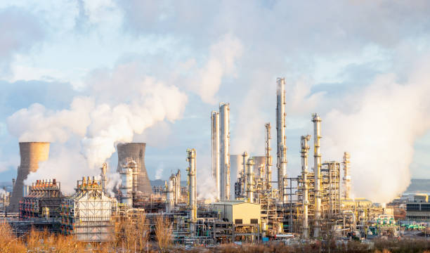 Oil Refinery and Petrochemical Plant at Grangemouth in Scotland Steam and smoke rising from distillation towers and cooling towers towards the left at Grangemouth oil refinery and petrochemical plant in Central Scotland. chemical plant stock pictures, royalty-free photos & images