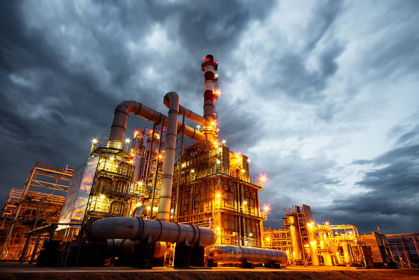 oil refinery at evening - refinery stock photos and pictures
