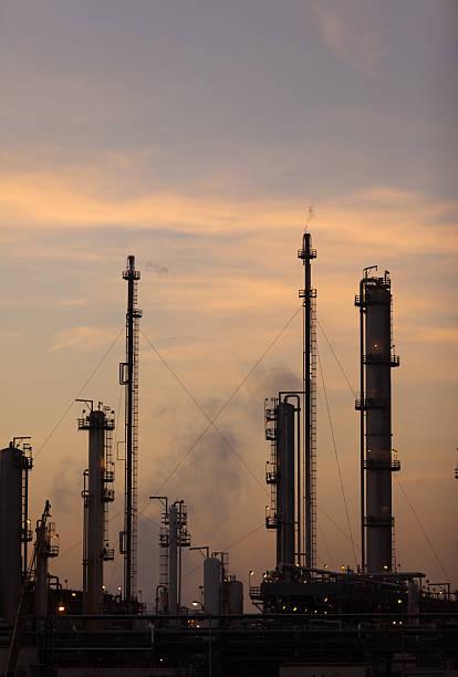 ölraffinerie bei sonnenuntergang - destillationsturm stock-fotos und bilder