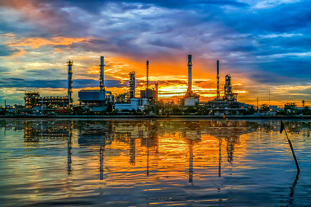 oil refinery at twilight and water reflection - refinery stock photos and pictures
