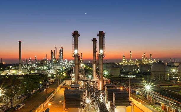 öl-raffinerie in der dämmerung - destillationsturm stock-fotos und bilder
