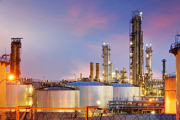 oil refinery at twilight - refinery stock photos and pictures