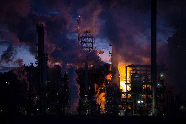 Oil refinery burning off gas at sunrise stock photo