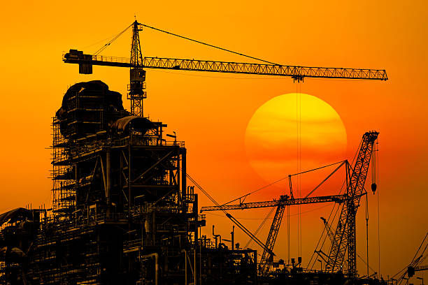 oil refinery construction in silhouette, industrial oil refinery in building - council flat stock photos and pictures