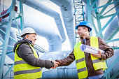 Oil refinery engineers successful deal handshake.