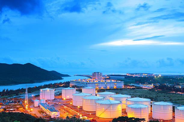 oil refinery factory pictured at dawn - brandstoftank stockfoto's en -beelden