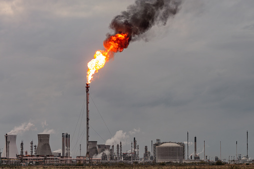 Environmental damage: A large flame and dark smoke rising from a flare stack at Grangemouth oil refinery and petrochemical plant in Scotland.