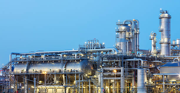 oil refinery iluminated at dusk - refinery stock photos and pictures