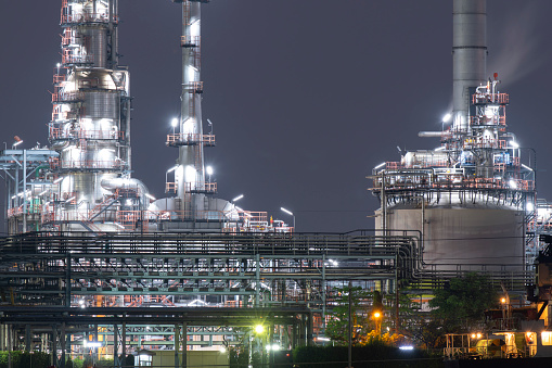 Oil refinery industrial district at night with tank farm and pipe line.