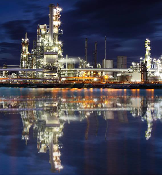 industrielle öl-raffinerie werk bei nacht - destillationsturm stock-fotos und bilder