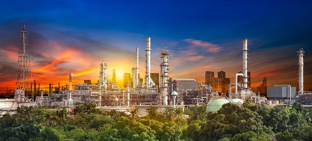 Oil refiner industry in rural scene on sunset background