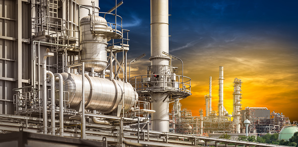 Structure of the oil refinery building on sunset background