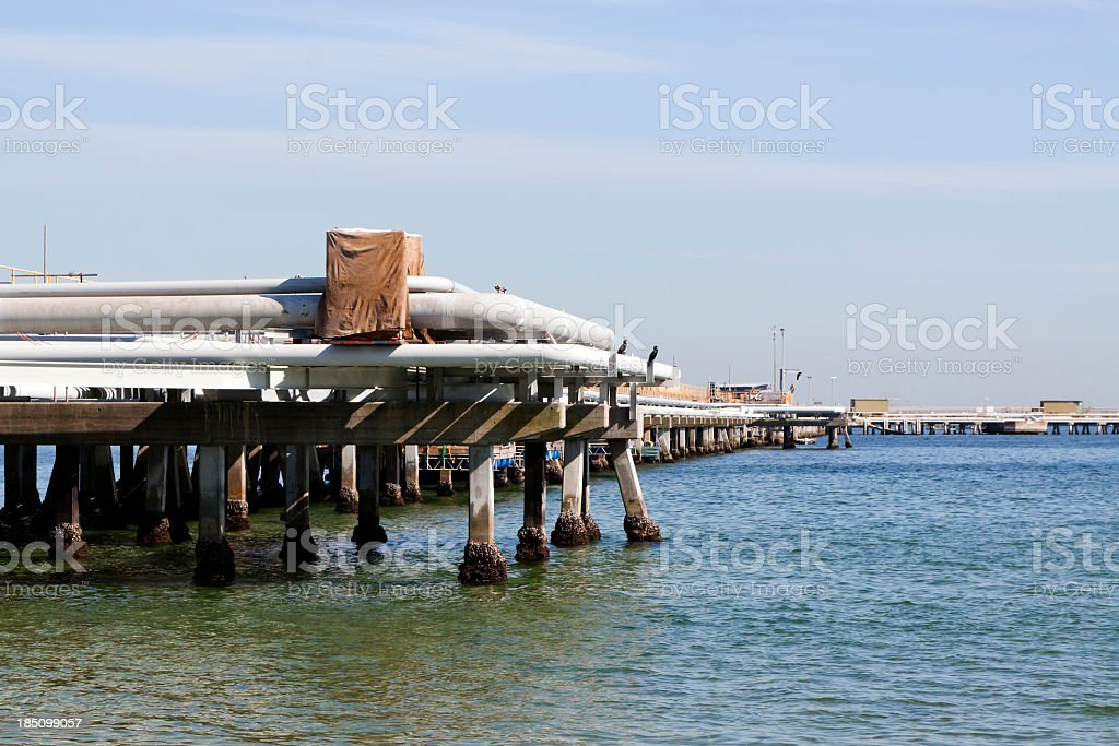 Oil refinery pipelines over bay on wooden pillars, copy space royalty-free stock photo