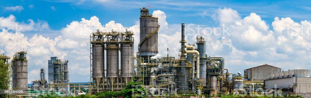 Öl-Raffinerie-Anlage hinter Reihe von Baum und blauer Himmel – Foto