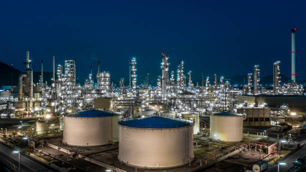 Oil refinery plant from industry zone, Aerial view oil and gas industrial, Refinery factory oil storage tank and pipeline steel at night. stock photo