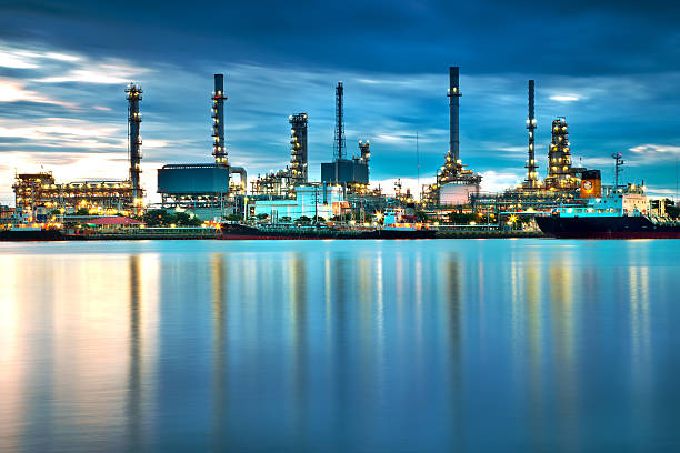 oil refinery with reflection, petrochemical plant - refinery stock photos and pictures