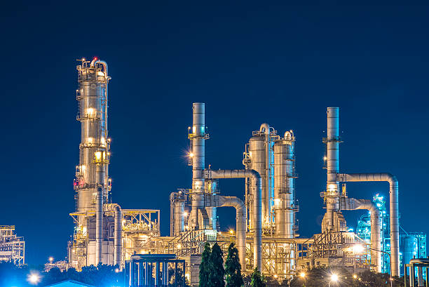 oil refinery with twilight sky - refinery stock photos and pictures