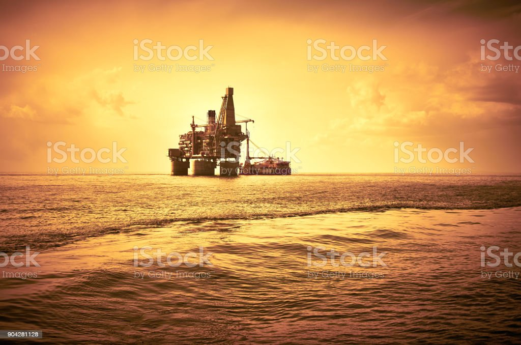 Oil rig and support vessel on offshore area, red sky sunset...
