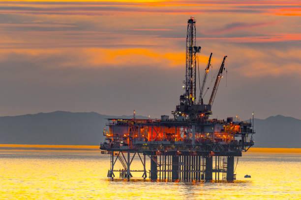Plataforma de petróleo e surfista da praia de Huntington na Califórnia - foto de acervo