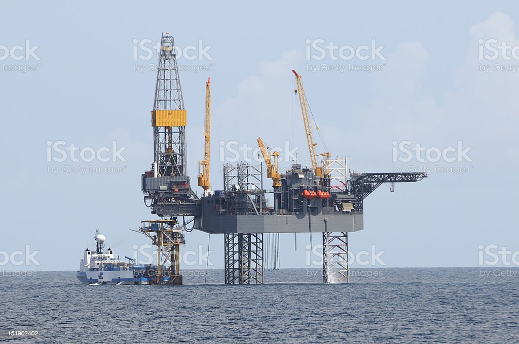 Oil rig and work vessel. (production or drilling platform.) stock photo