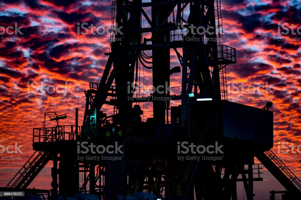 Oil Rig at cloudy sunset stock photo