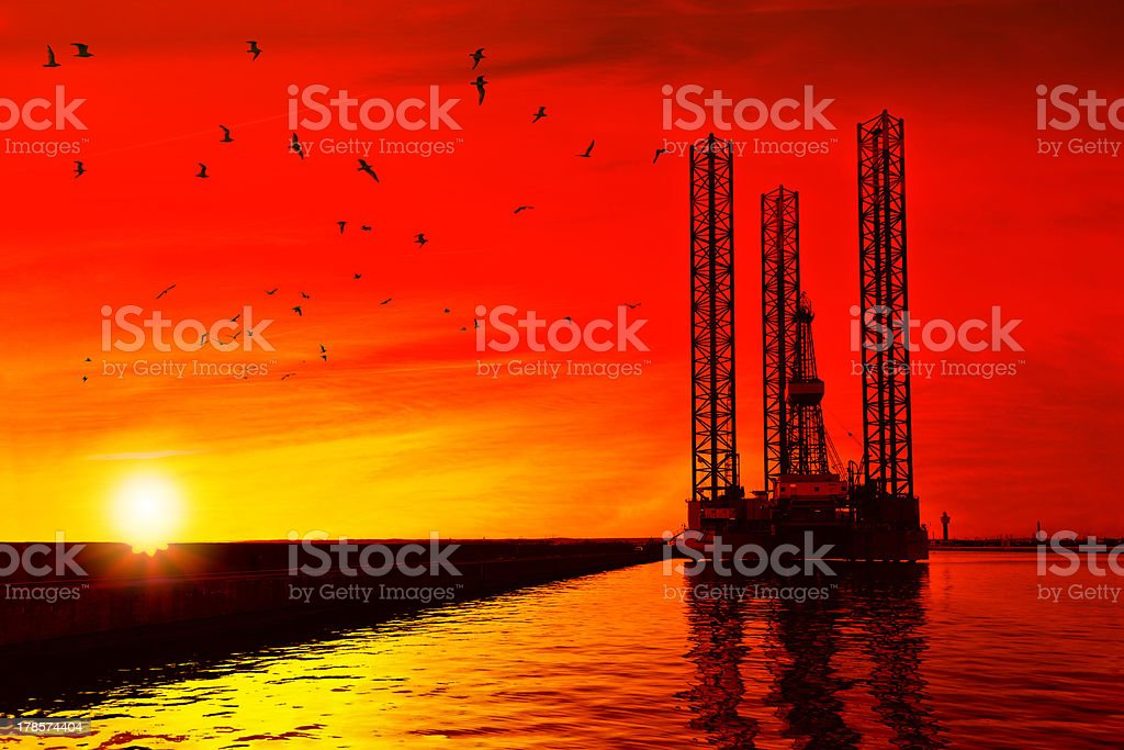 Oil rig at sunset stock photo