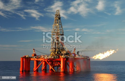 An oil rig situated in a calm blue ocean exploring for oil and gas. The oil rig is flaring from the side and this is reflected in the ocean. Fluffy white clouds are scattered in a blue sky.