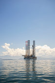 Off Shore oil rig drilling platform structure reflects on calm blue seas
