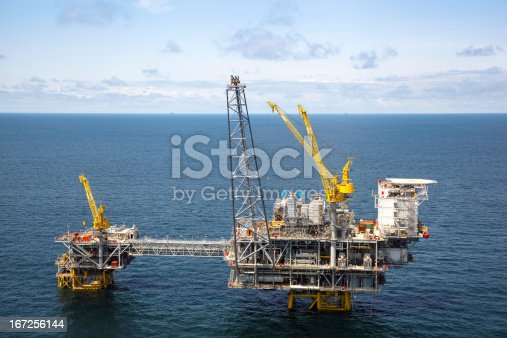 Low level aerial photo of a large offshore oil rig, with two more oil rigs in the distance. One is an FPSO, the other a large semi-sub drilling rig.