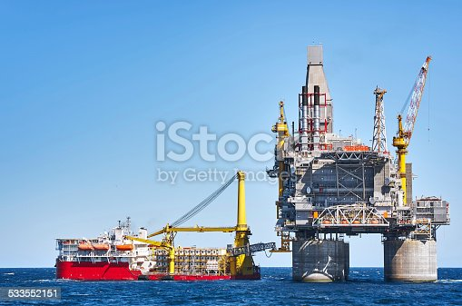 Oil rig and support vessel on offshore area near Sakhalin island. Blue sky background