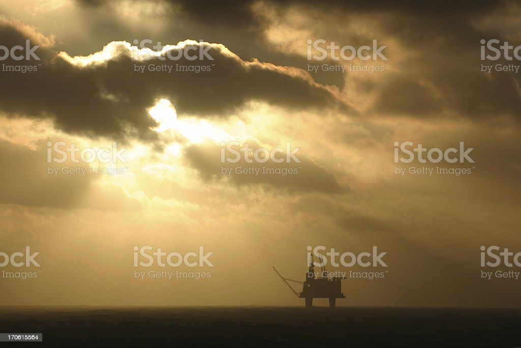 oil rig platform at sea with sun setting royalty-free stock photo