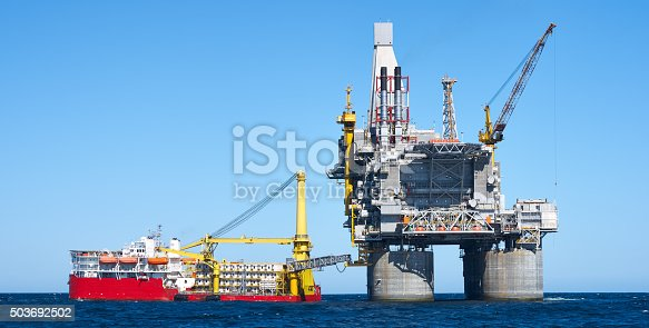 Oil rig and support vessel on offshore area. Blue sky, sea. photomerge