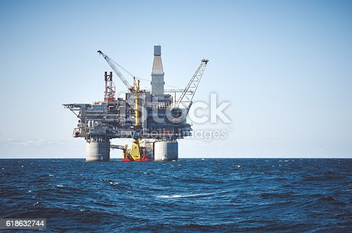 Oil rig and support vessel on offshore area. Blue clear sky, sea