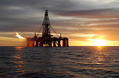 An ocean oil rig flaring natural gas at sunset.